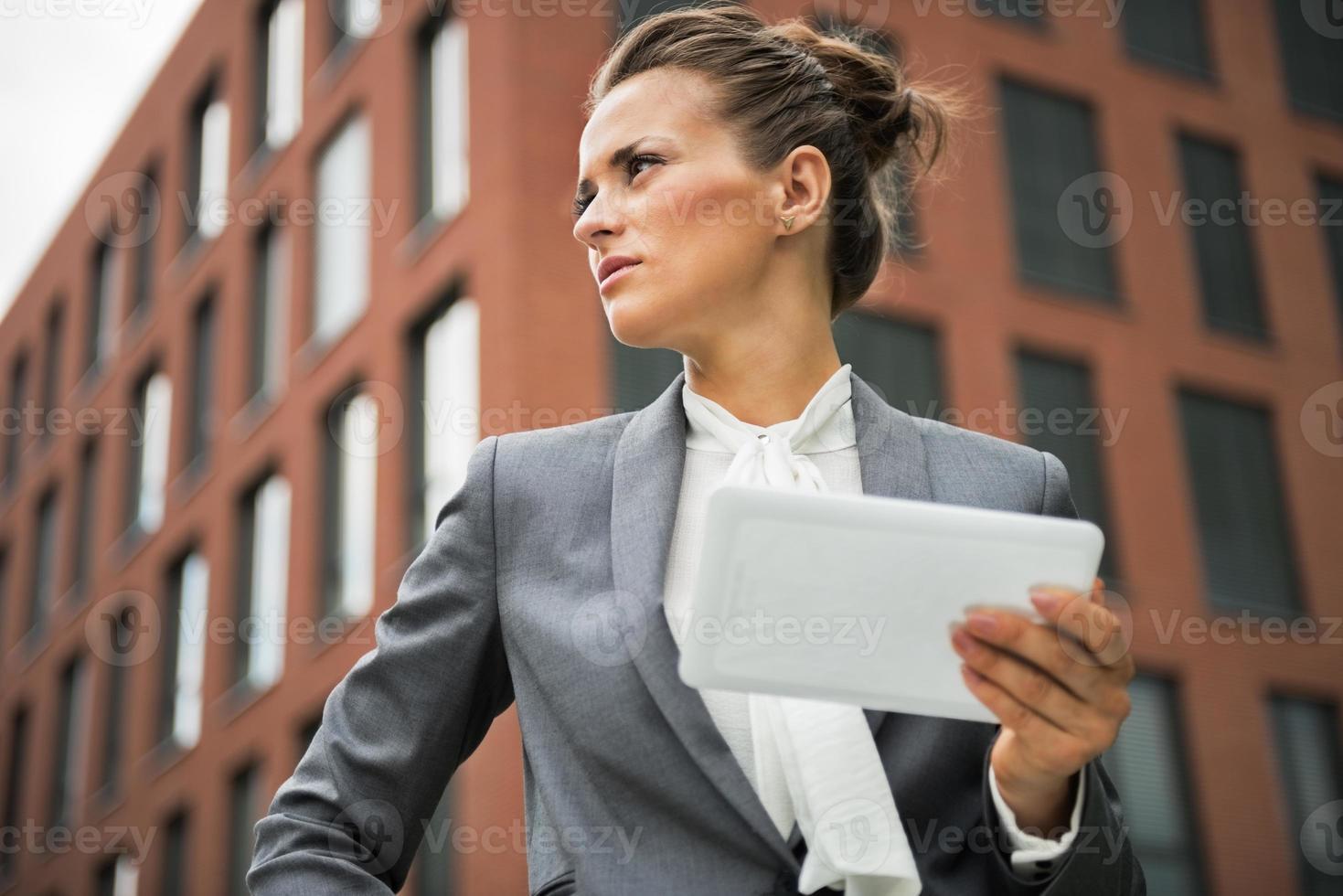 donna d'affari con tablet pc davanti all'edificio per uffici foto