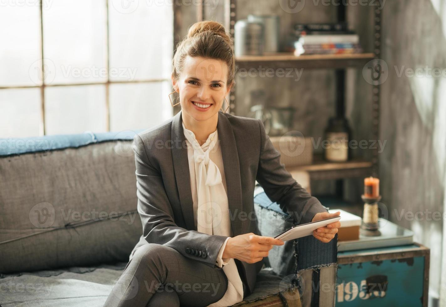 donna felice di affari che utilizza il pc della compressa nell'appartamento del sottotetto foto