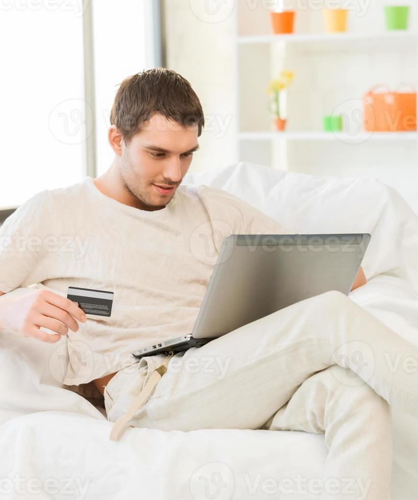 giovane con laptop e carta di credito a casa foto