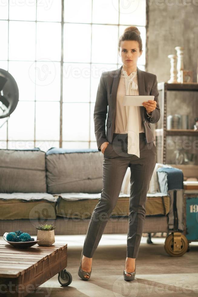 donna d'affari riflessivo utilizzando tablet pc in appartamento loft foto