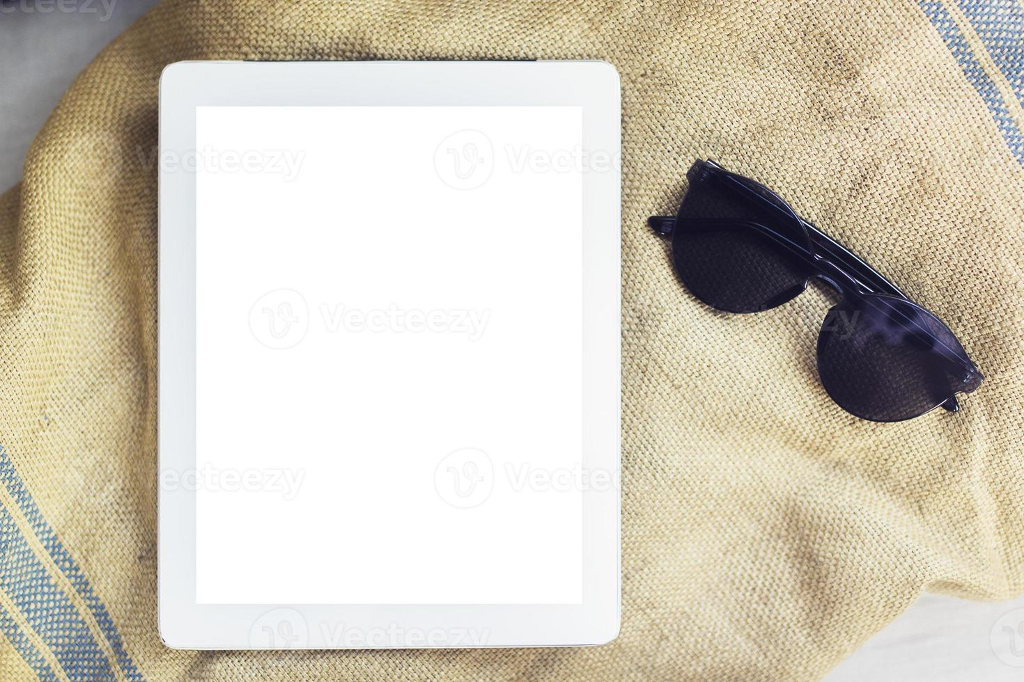 tavoletta digitale vuota con occhiali da sole su un asciugamano, mock up foto