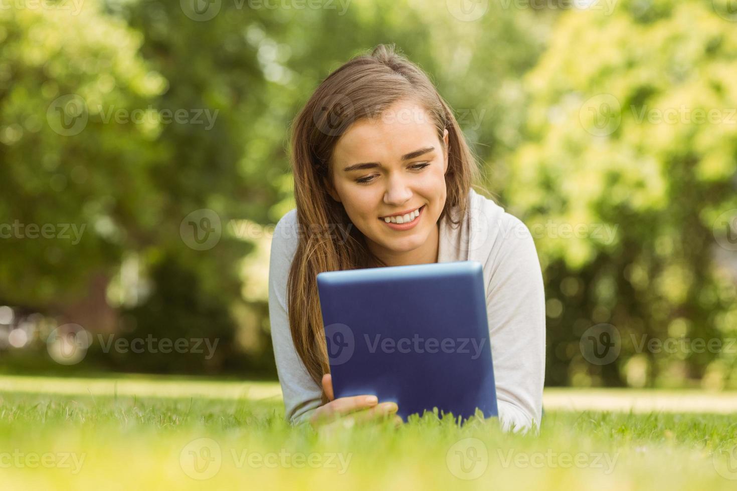studente universitario sorridente sdraiato e utilizzando tablet pc foto