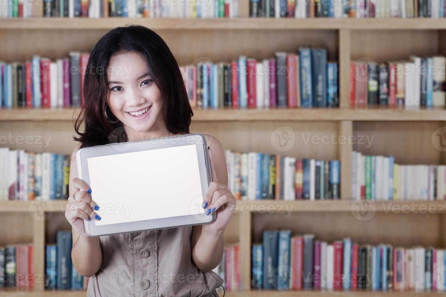 scolara che mostra uno schermo del tablet in biblioteca foto