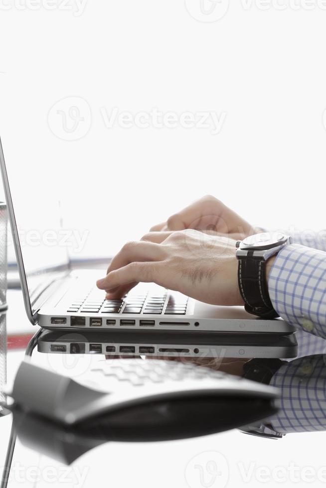 primo piano dell'uomo d'affari che lavora al computer portatile, contro il backgro bianco foto