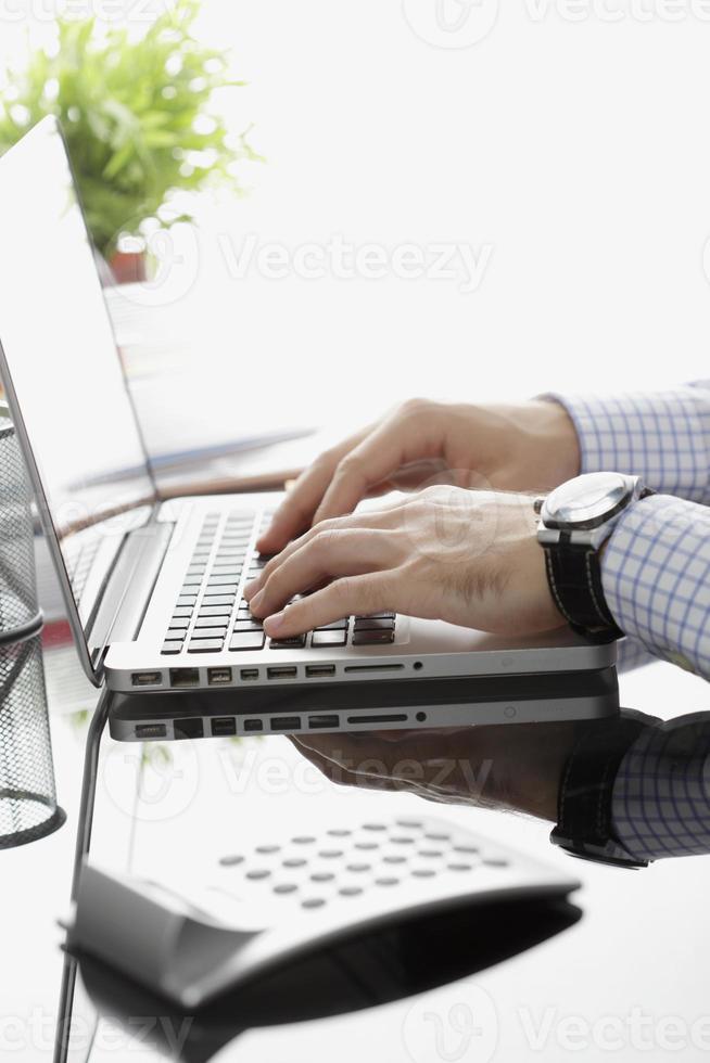 primo piano dell'uomo d'affari che lavora al computer portatile foto