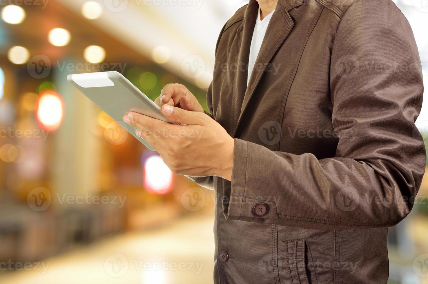 mani del giovane che tengono compressa nel centro commerciale foto