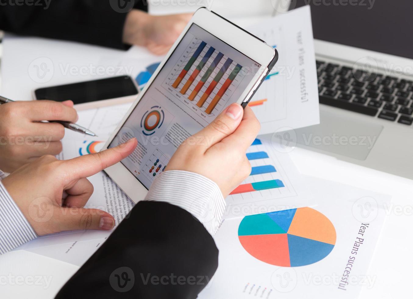 squadra di affari che analizza i modelli di business facendo uso della compressa digitale foto