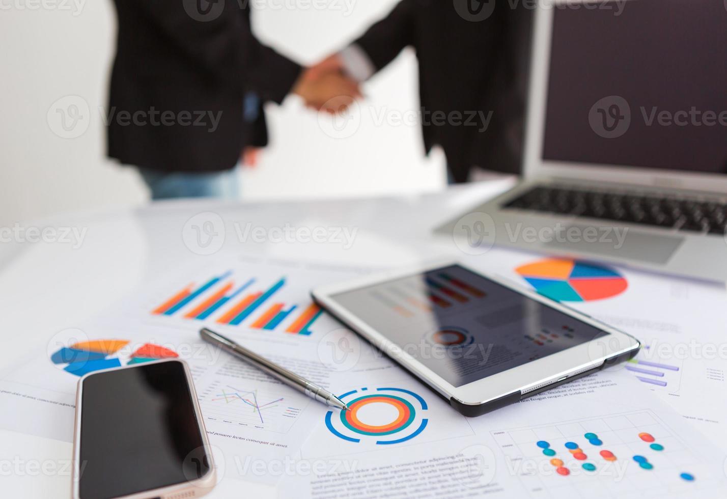 primo piano del gruppo di affari che per mezzo della compressa digitale con finanziaria d foto