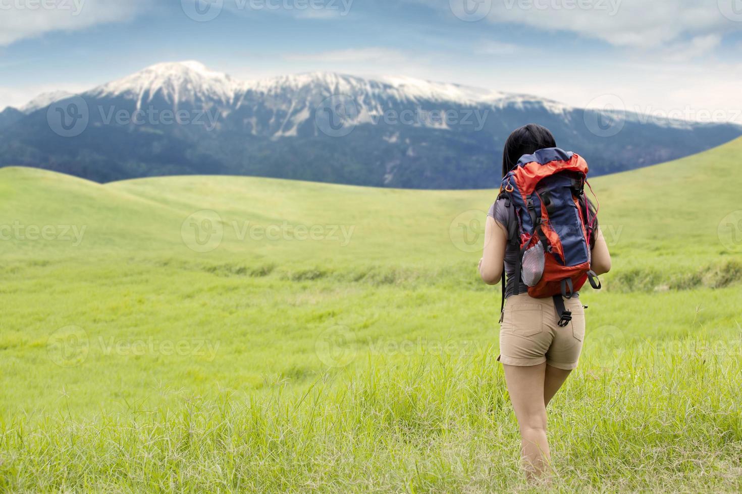 escursionista che cammina verso la montagna foto