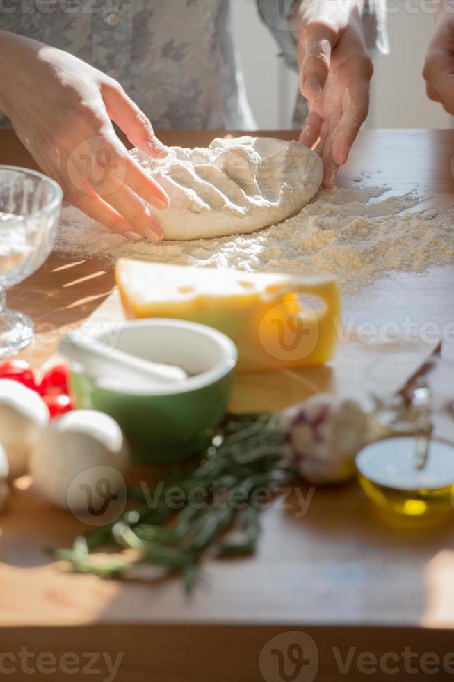 una donna che produce un impasto per una pizza a casa foto