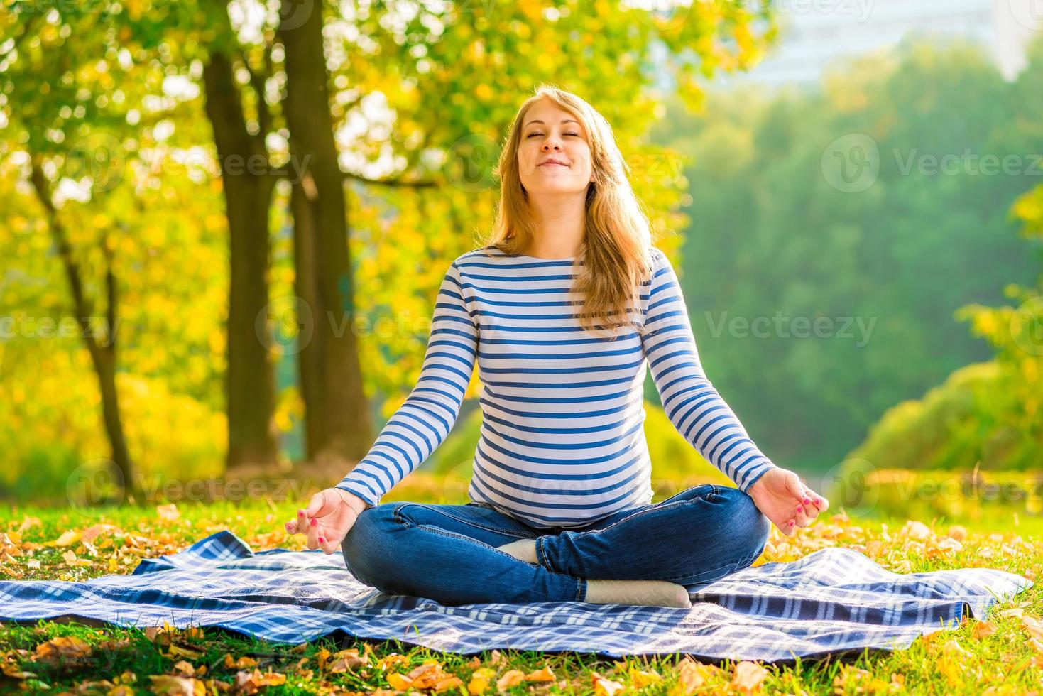 la donna incinta nella posizione del loto esegue esercizi di respirazione foto