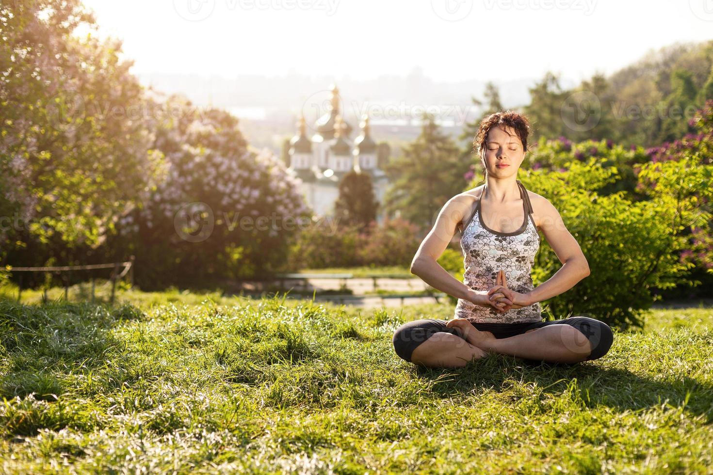 giovane donna che medita nella posizione di loto all'aperto foto