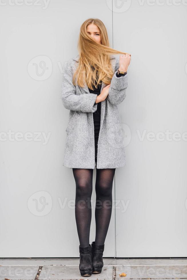 donna dei capelli biondi che cammina sulla strada e sorriso foto
