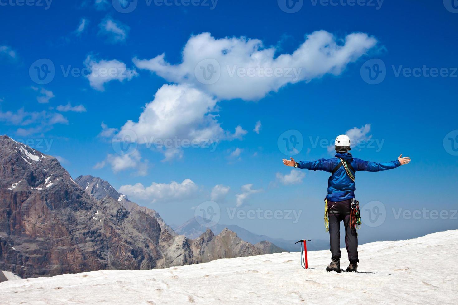scalatore godendo sulla cima della neve foto