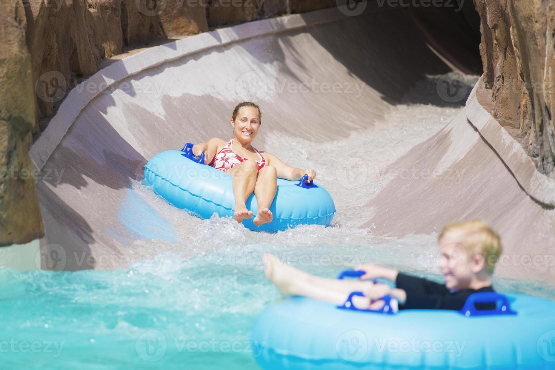famiglia godendo un giro bagnato lungo uno scivolo d'acqua foto
