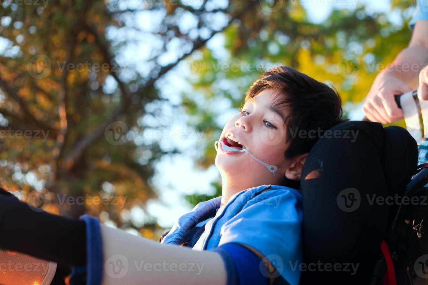 bel ragazzino disabile in sedia a rotelle, godendo il tramonto all'aperto foto