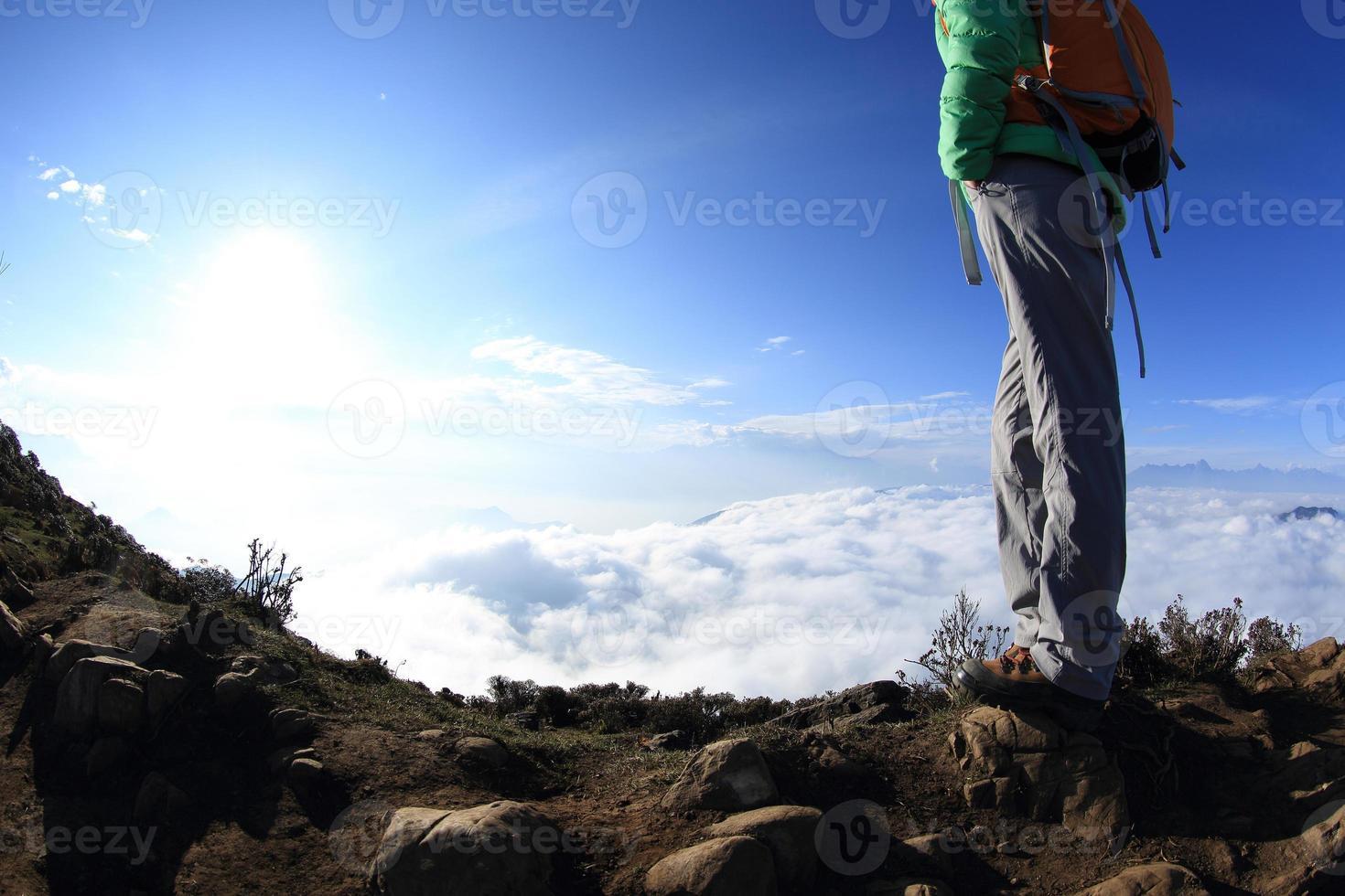 le gambe dell'escursionista sul picco di montagna del tramonto godono della vista foto