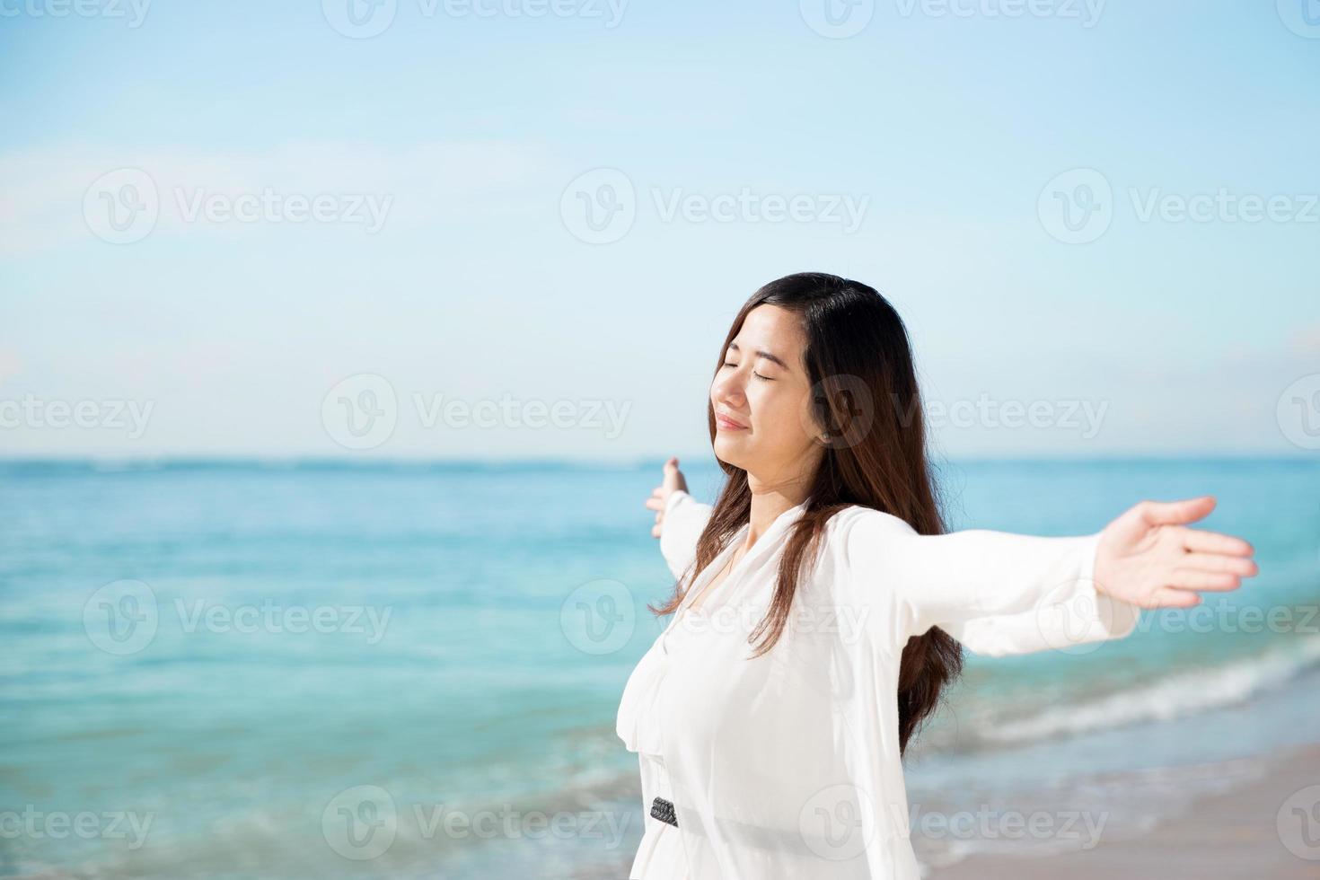 donna asiatica che gode della spiaggia, chiudere gli occhi e le braccia aperte foto
