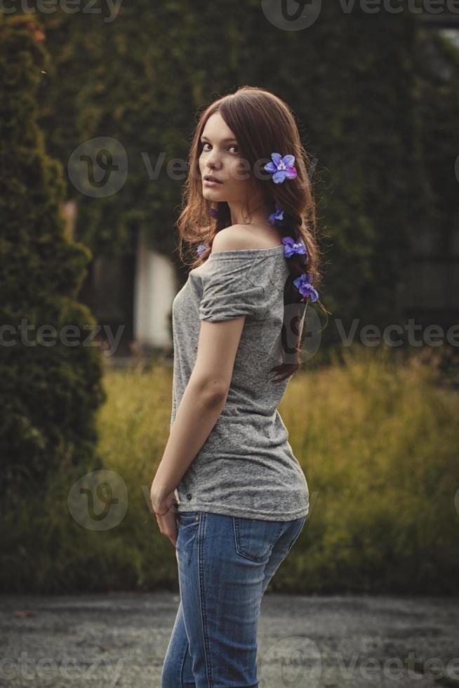 giovane e bella donna all'aperto in giardino al tramonto, fiori nei capelli foto