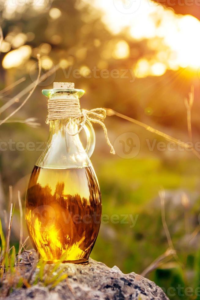 bottiglietta con olio d'oliva con riflesso lente e luce solare foto