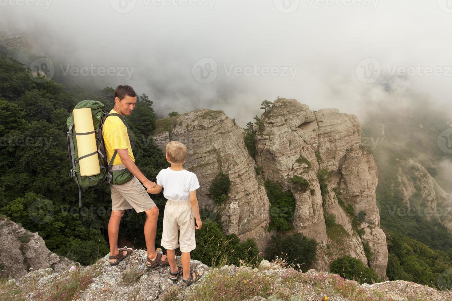 zaino in spalla con figlio piccolo tra le montagne nebbiose. foto