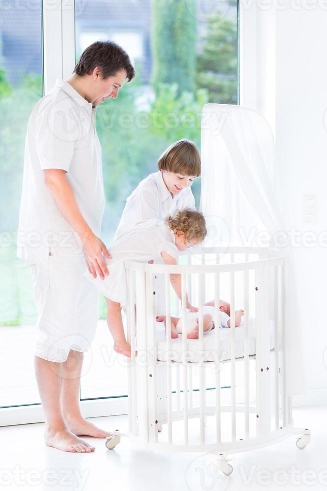 padre felice con i bambini accanto culla a guardare il bambino appena nato foto