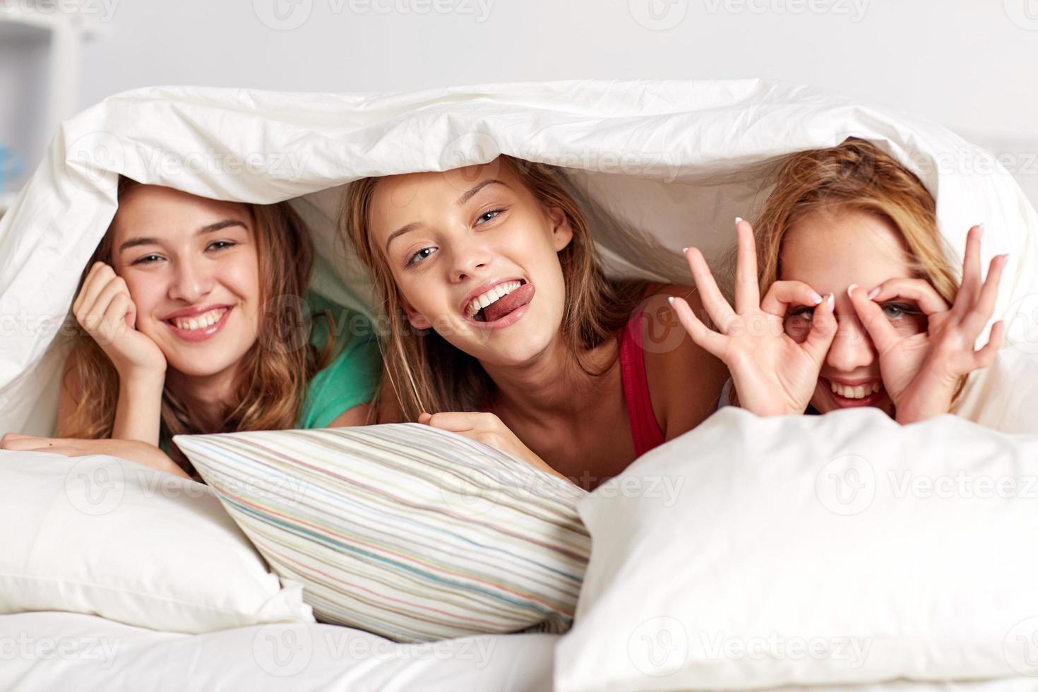 felice giovane donna a letto a casa pigiama party foto