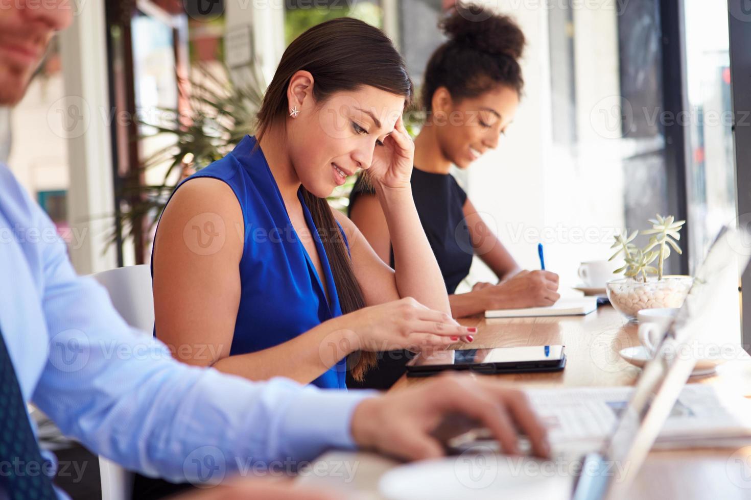 donna di affari che utilizza compressa digitale nella caffetteria foto