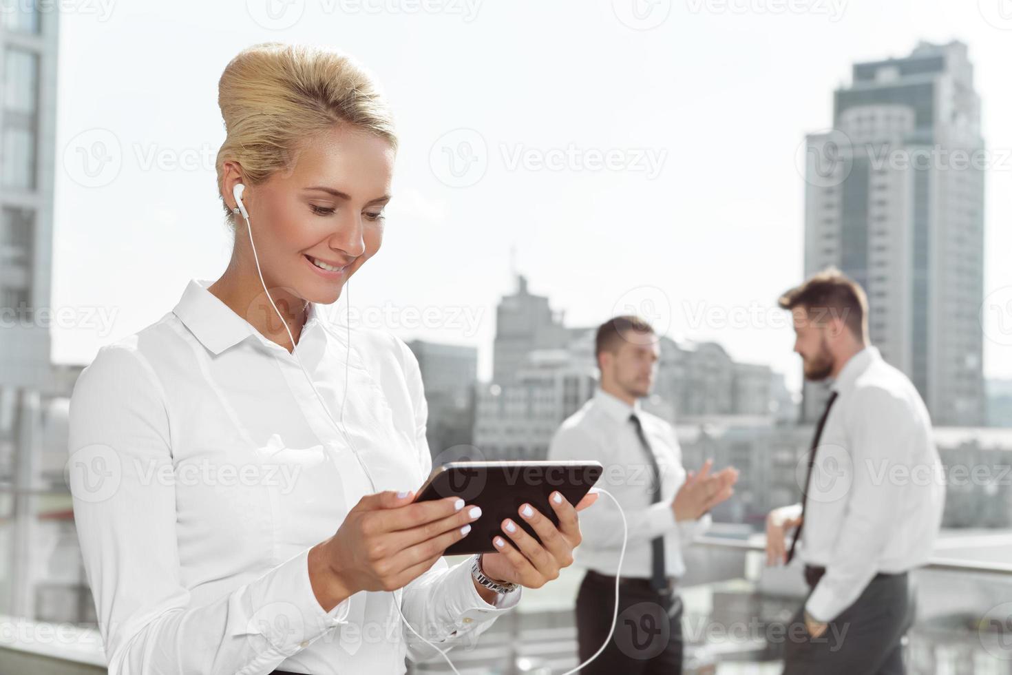 donna di affari attraente che per mezzo della compressa all'aperto foto
