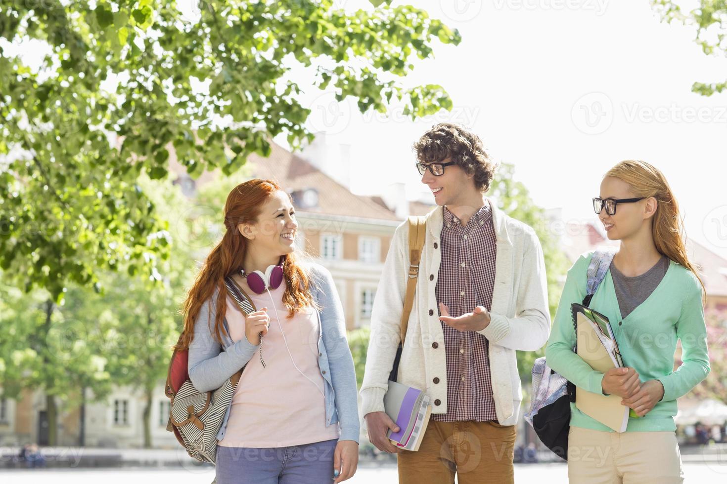 giovani studenti universitari che parlano mentre si cammina sulla strada foto