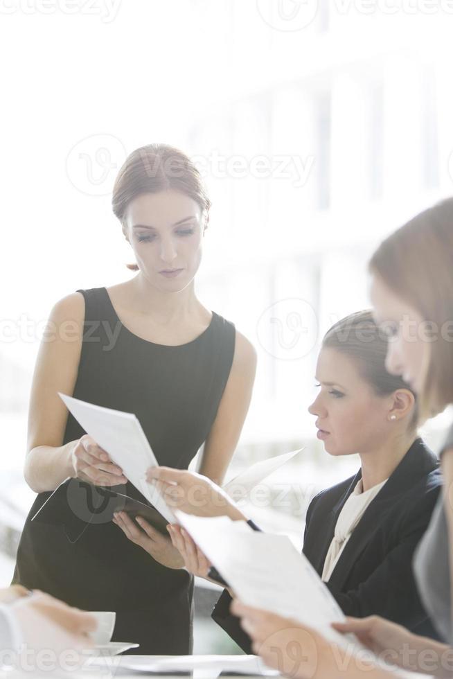 donne d'affari facendo scartoffie durante la pausa caffè foto