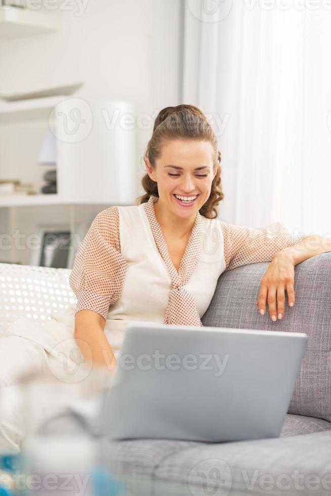 giovane casalinga felice che utilizza computer portatile nel salone foto