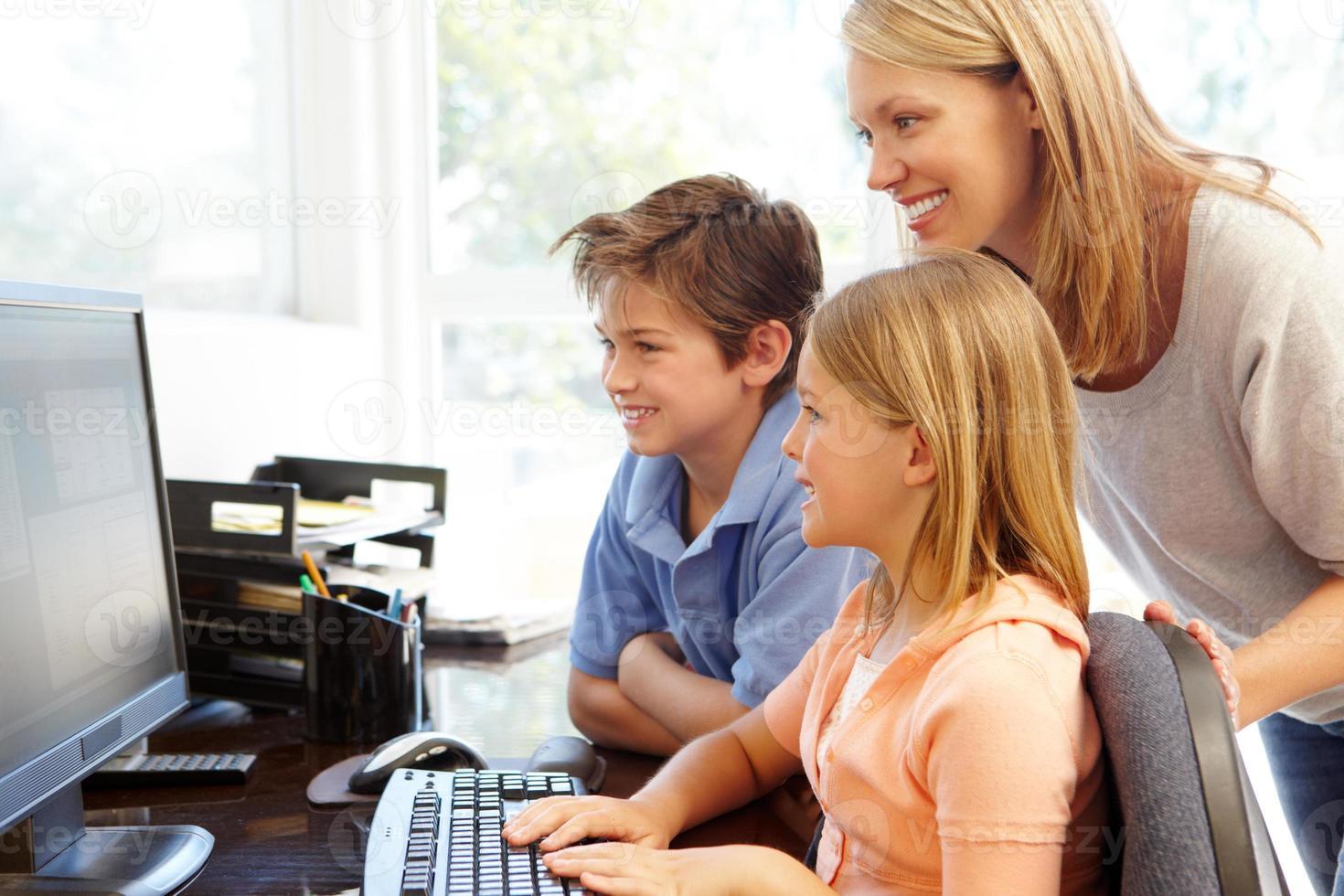madre e figli che usano il computer a casa foto