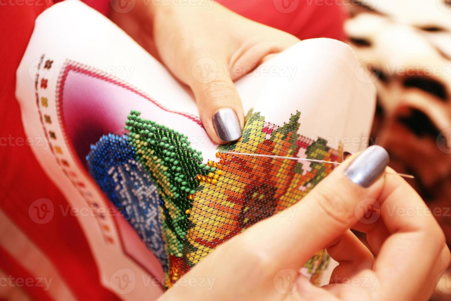 processo di ricamo sulle mani di perline di tessuto foto