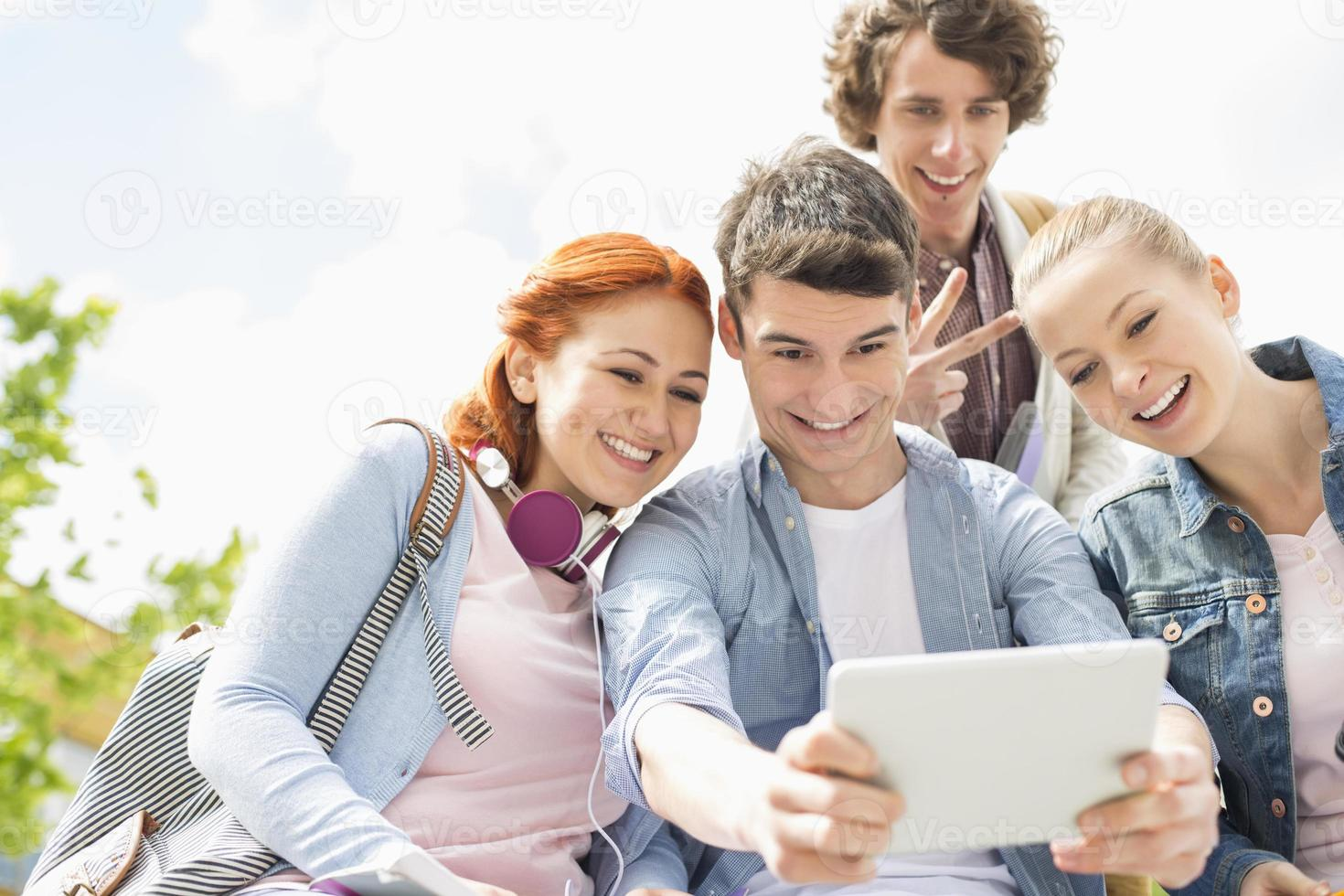 giovani amici che si fotografano attraverso la tavoletta digitale nel campus universitario foto