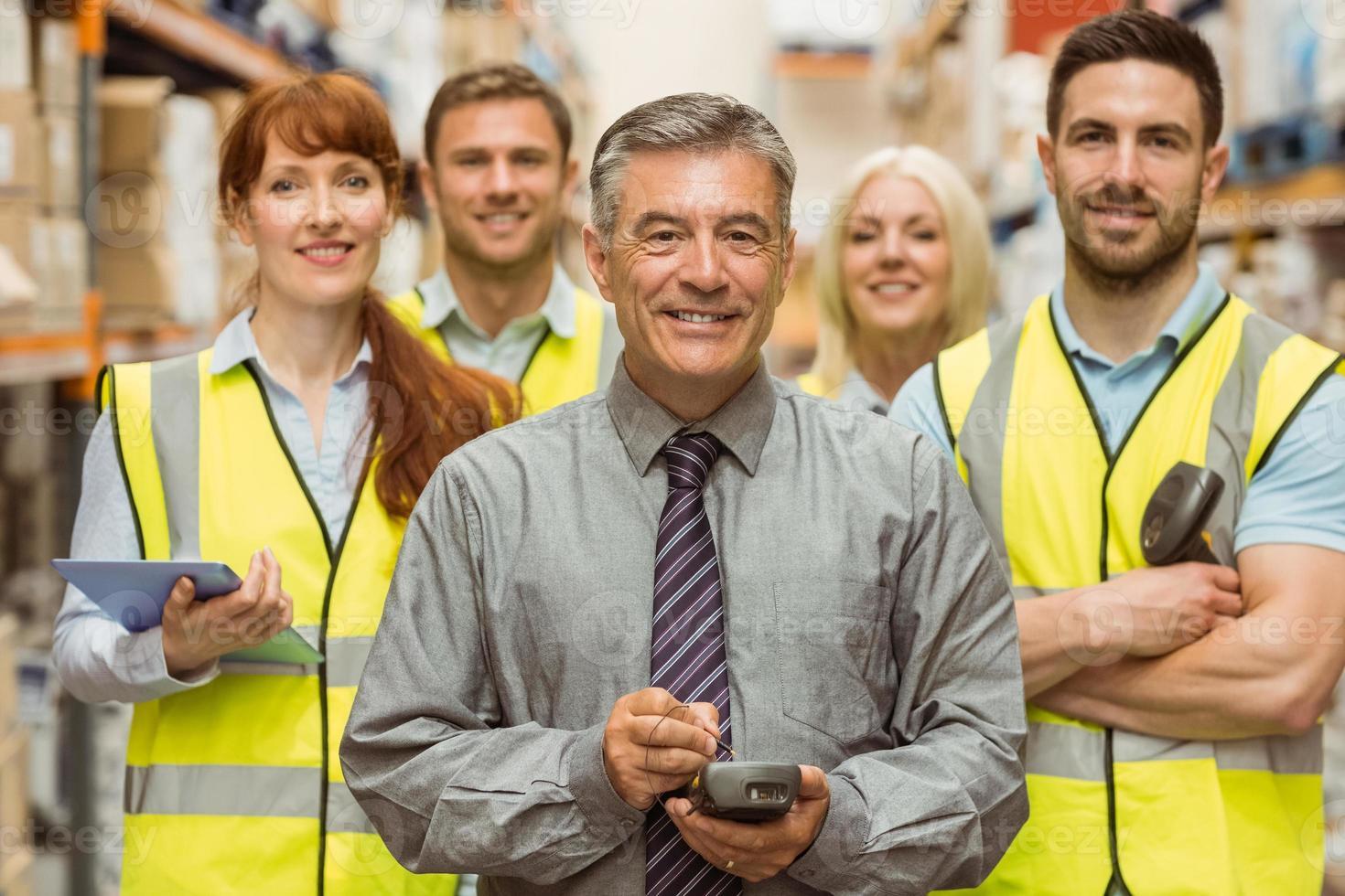 sorridente squadra di magazzino con le braccia incrociate foto