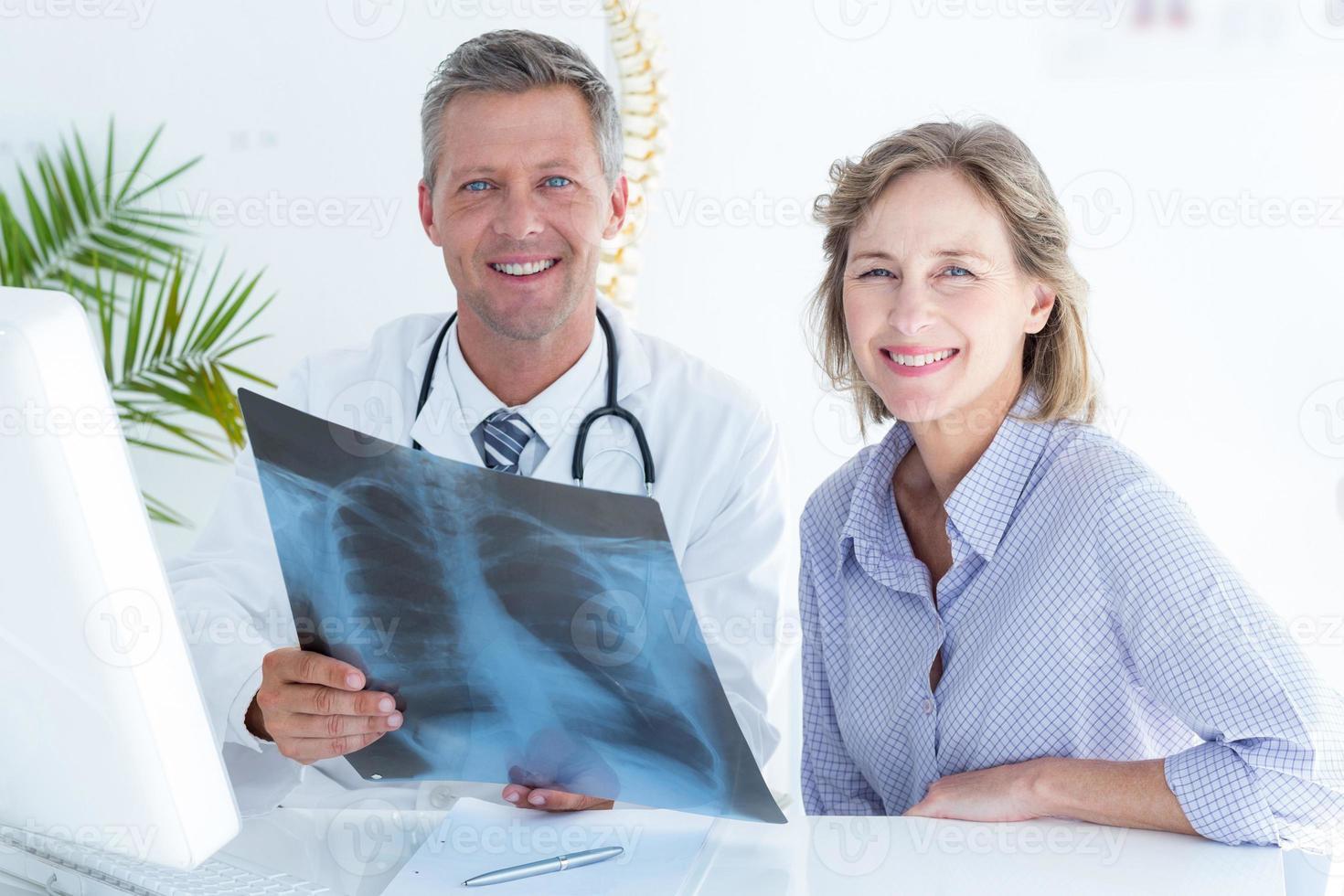 medico e paziente che sorridono alla macchina fotografica foto