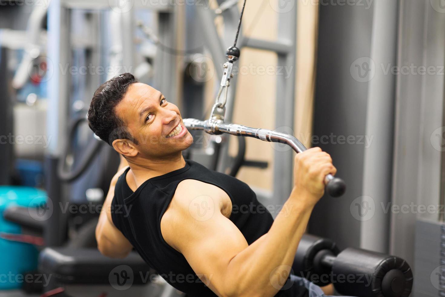 uomo di mezza età facendo allenamento pull-down foto