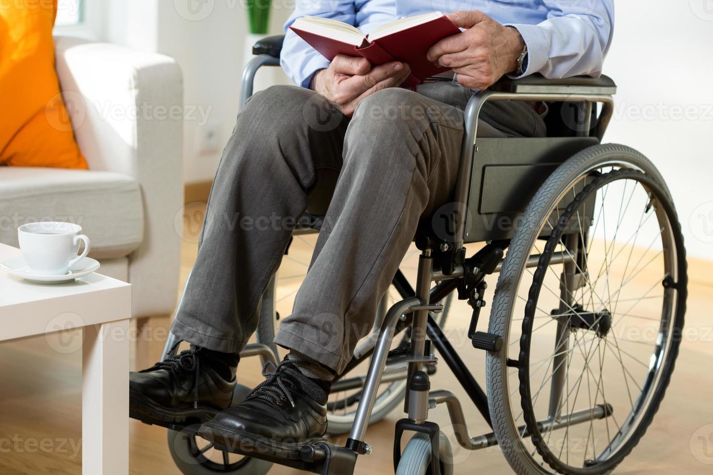 uomo su sedia a rotelle, leggendo un libro foto
