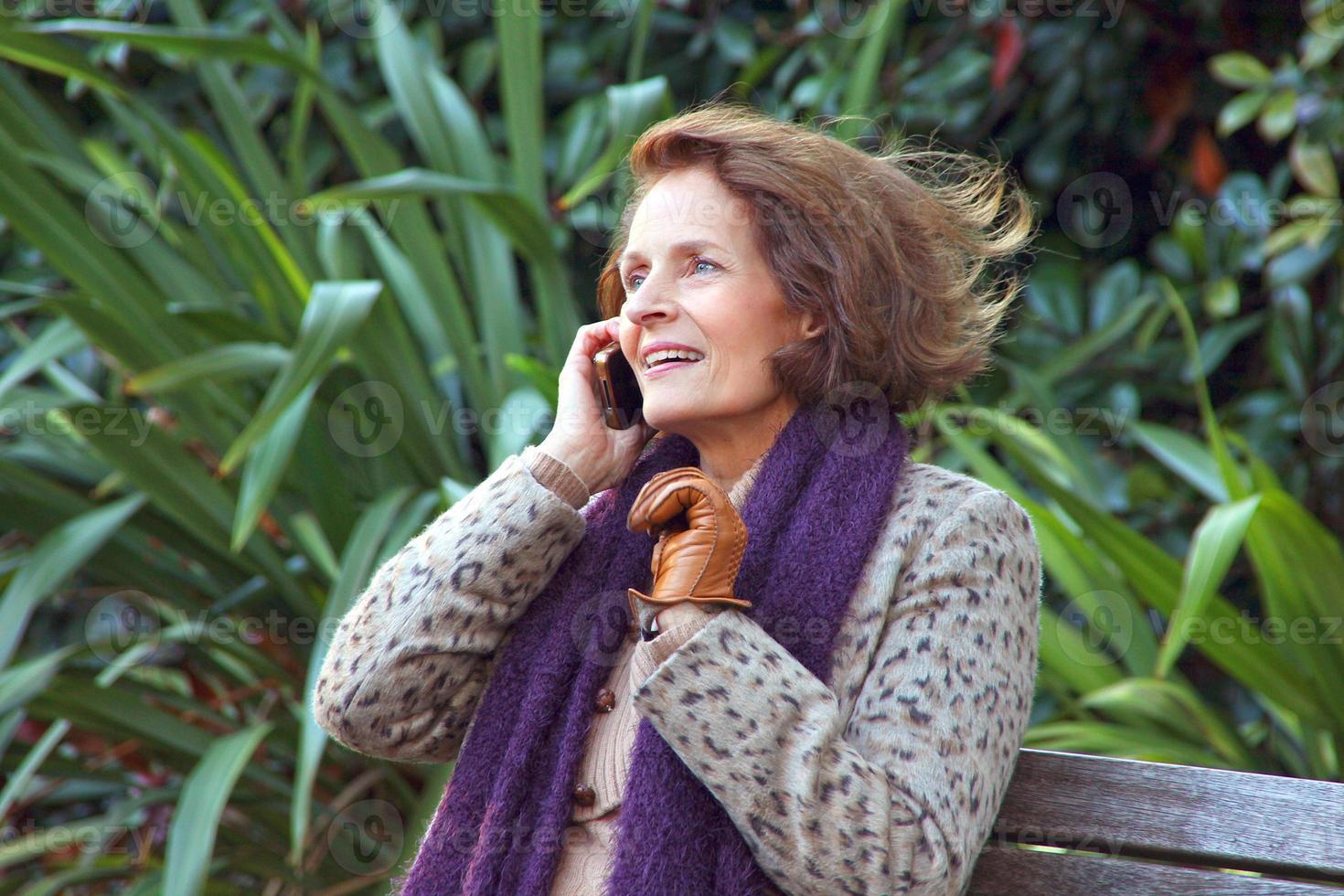 signora matura nel parco il suo telefono cellulare. foto