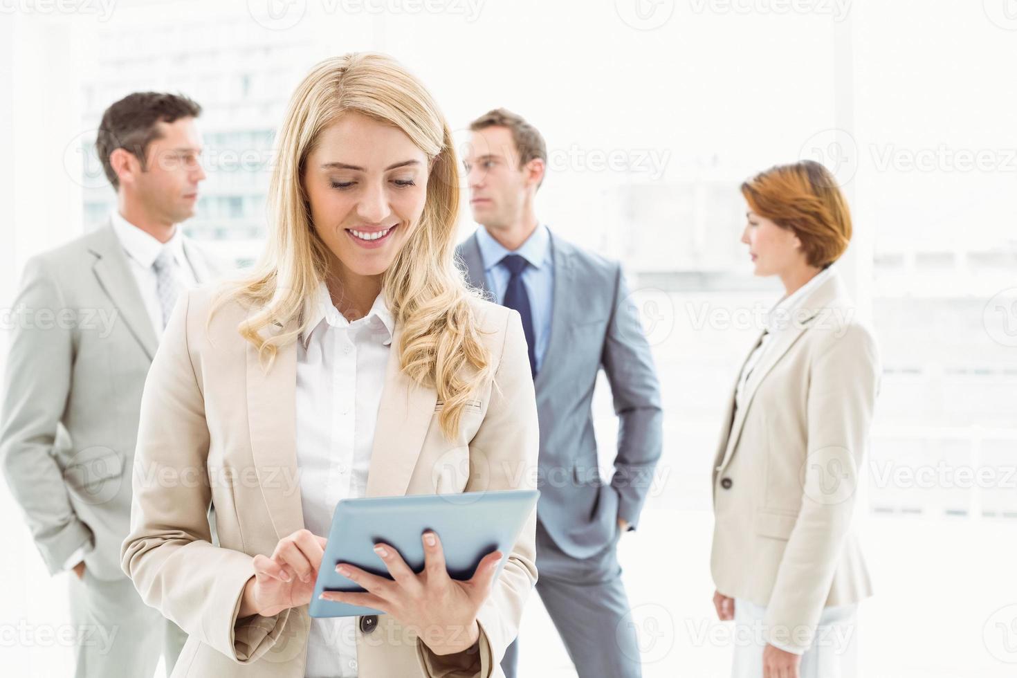 imprenditrice utilizzando la tavoletta digitale con i colleghi dietro foto