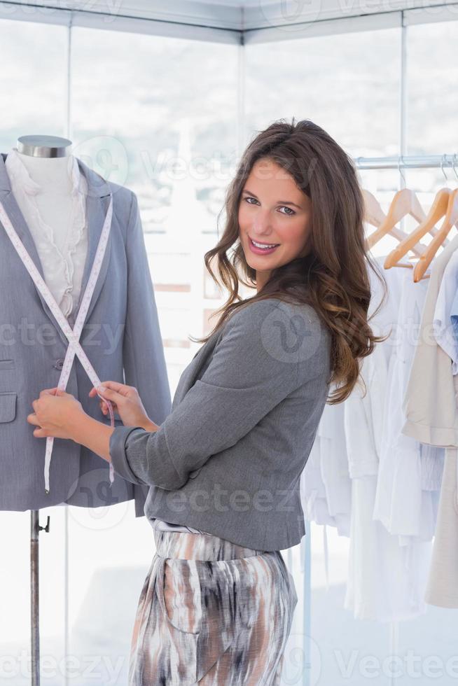 stilista attraente che misura bavero del blazer foto
