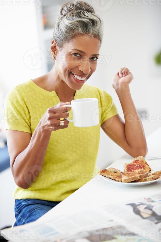 donna matura che mangia prima colazione e che legge giornale foto