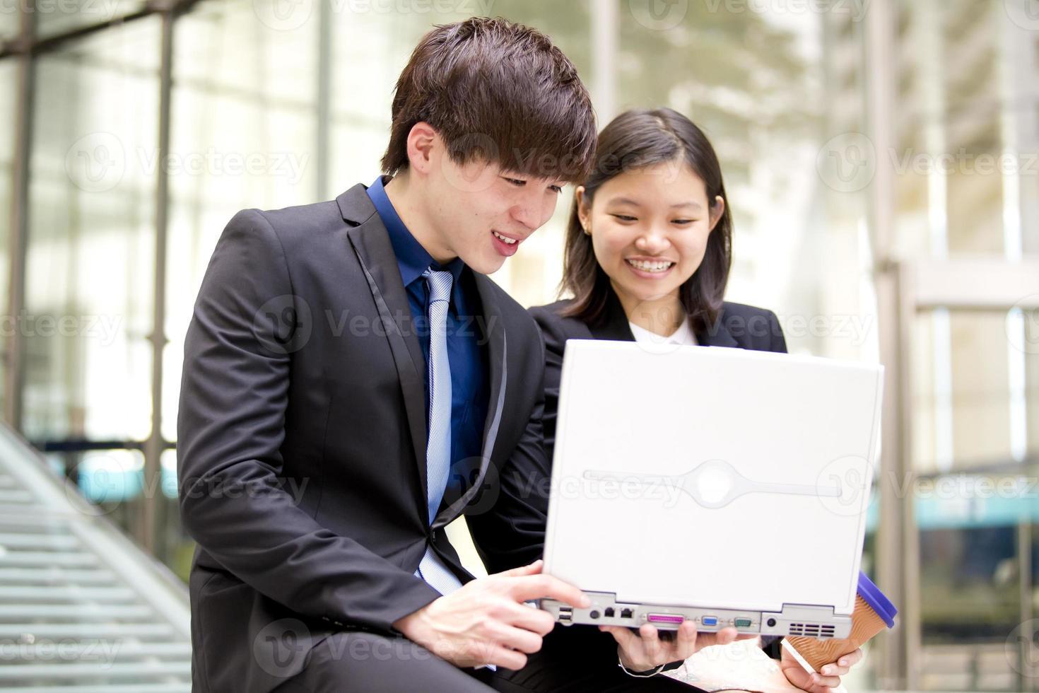 giovane uomo d'affari asiatico maschio e femmina con laptop foto