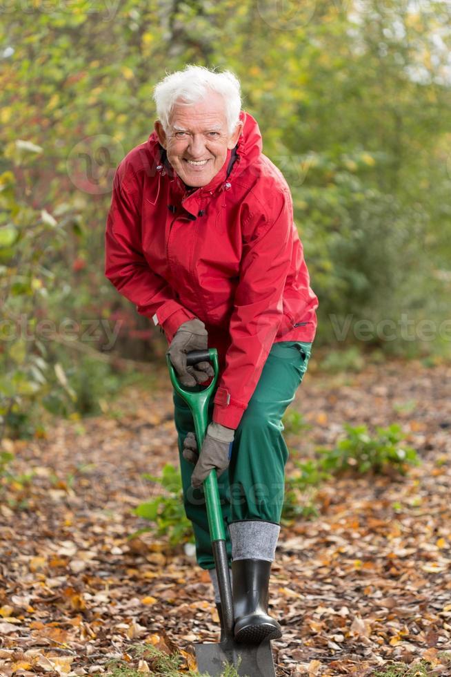 uomo senior con la vanga in giardino foto