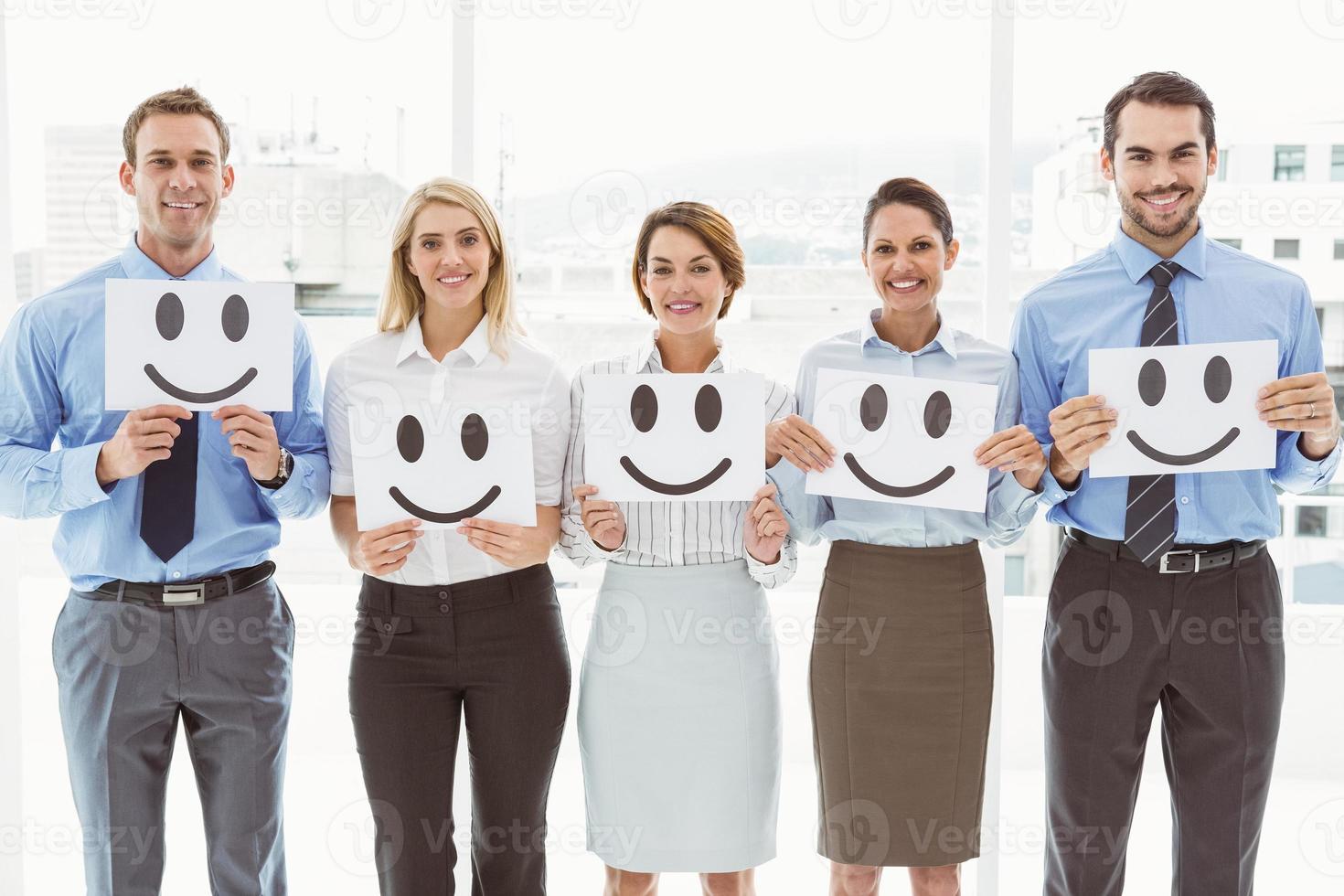 uomini d'affari in possesso di faccine felici in ufficio foto