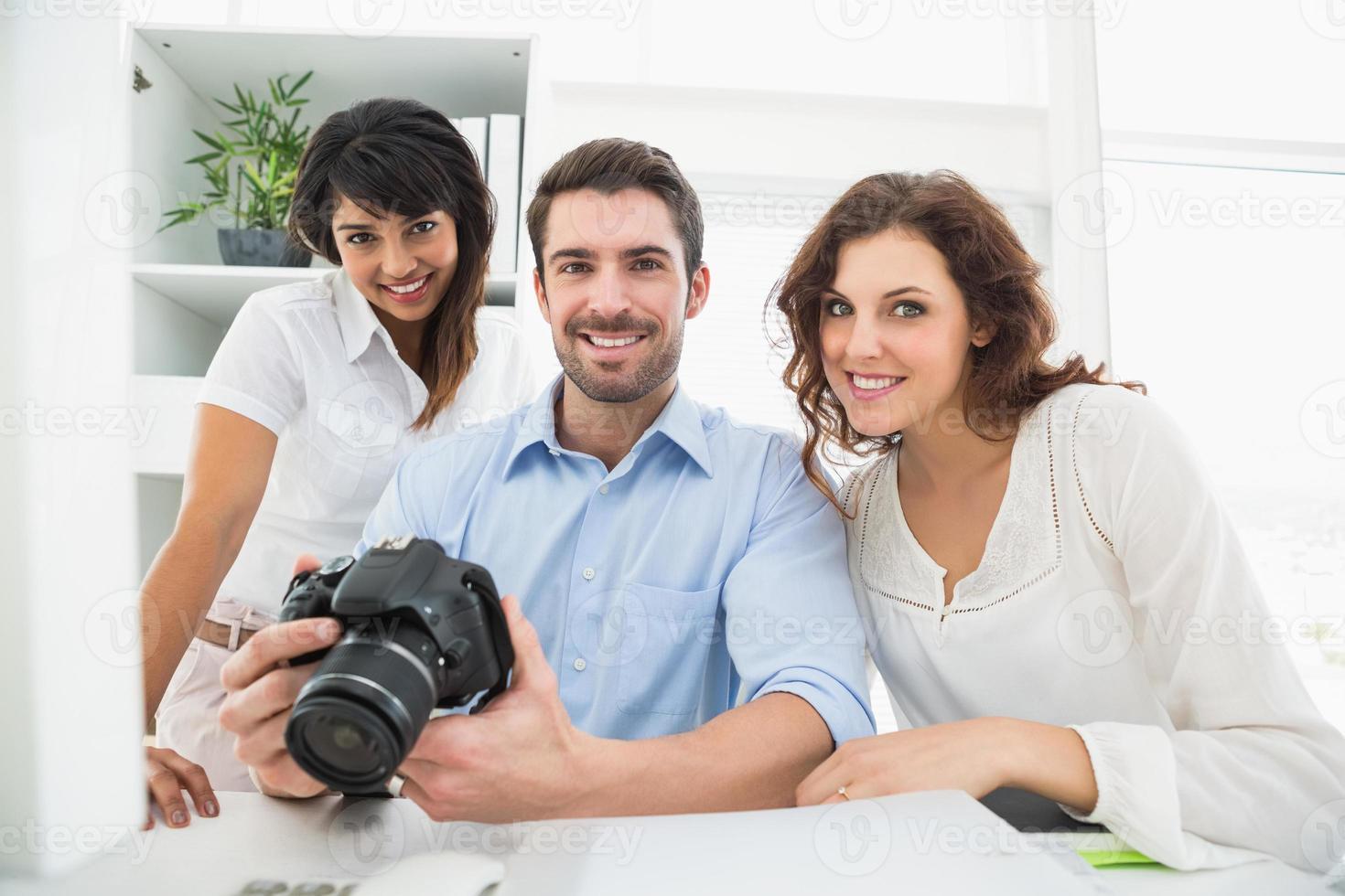 felice lavoro di squadra in posa con la fotocamera digitale foto