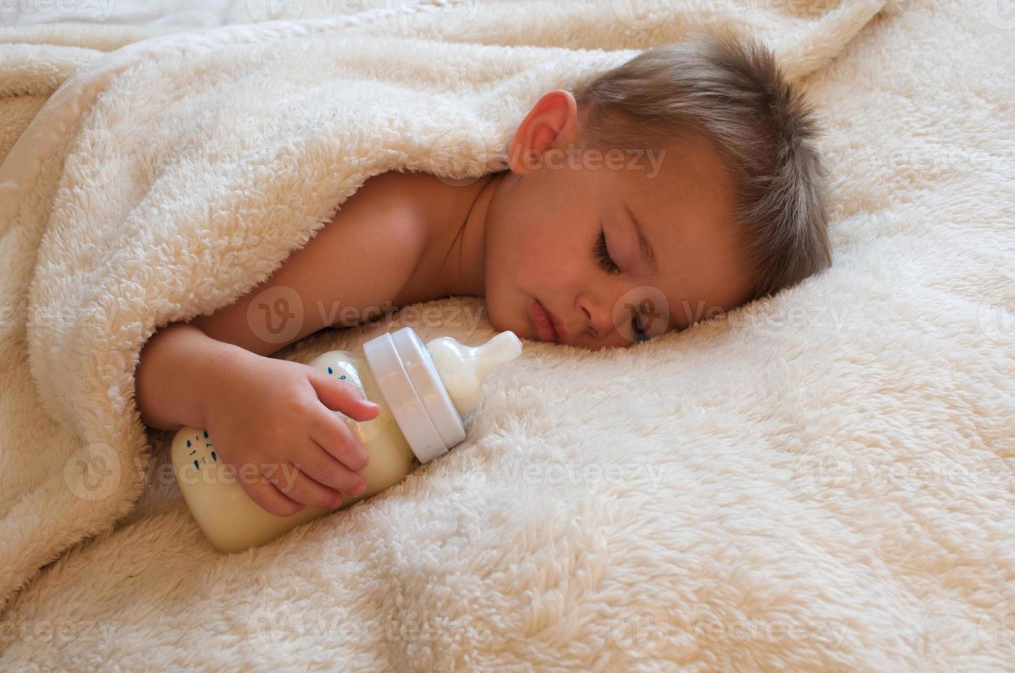 bambino che dorme con biberon foto