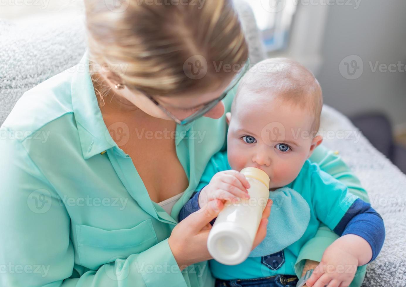 carino bambino che si imbocca da una bottiglia foto