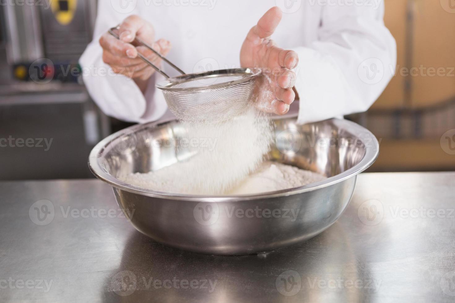 fornaio setacciare la farina in una ciotola foto